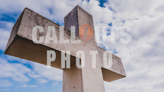 Heavy Stone Cross with Cloudy Sky Backdrop