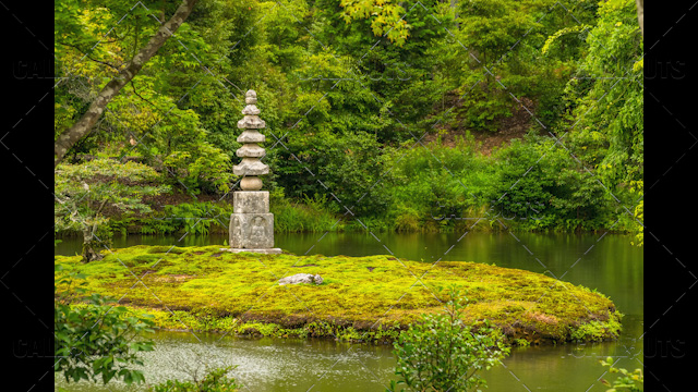 Japanese stone pagoda on an island in a garden pond or lake