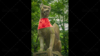 Fushimi Inari-taisha shrine, fox statue with red scarf. Kyoto, Japan.