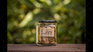 A Jar with Coins with a Save Note Inside, Centered