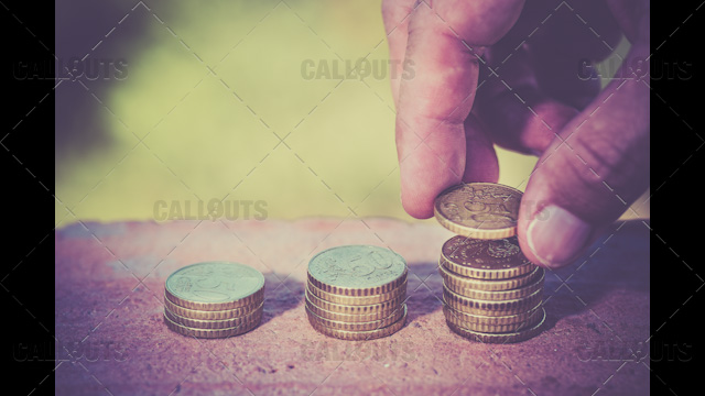Hand Stacking and Counting Coins on Brick