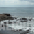 Hidden Beach Cove. Waves Crashing Over Rocks in Stone Shoreline Landscape, Evoking a Sense of Freedom. Cloudy Skies in Distant Background. Slow Motion Fixed Shot.