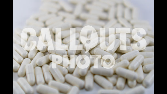 Pile of White Medicine or Supplements, White Background, Shallow Depth-of-Field