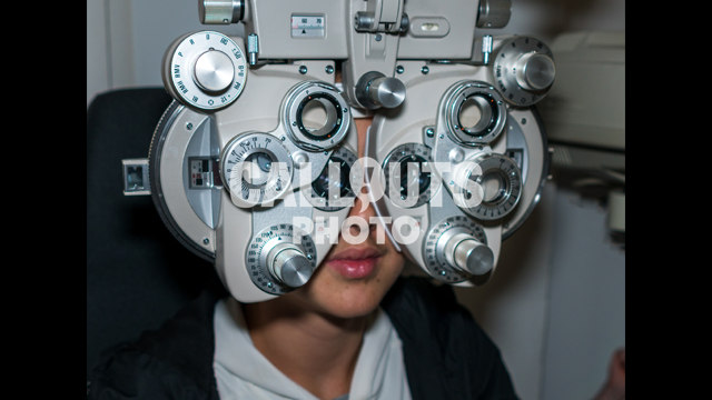 Young Teenage Boy Going Through Eye Exam, Ophthalmic Testing Device