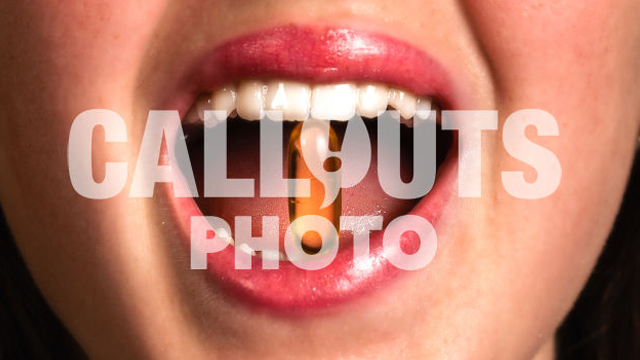 Closeup of Young Womans Mouth Biting Medicine or Supplement, Closeup of Mouth