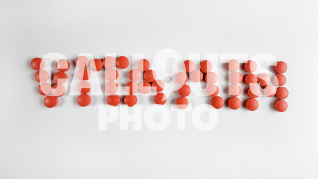 Red Medicine or Supplement Pills Forming the Text Vitamin on White Background
