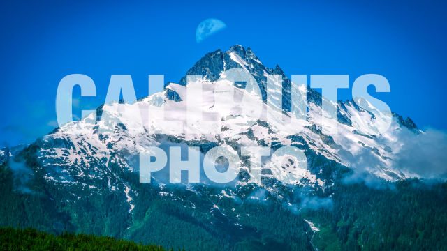 Snow covered mountain top with moon