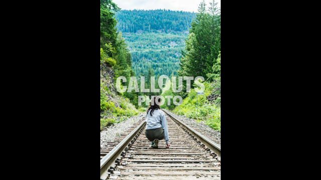 Girl on straight railroad tracks through dense forest